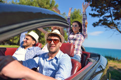 Leisure, road trip, travel and people concept - happy friends driving in cabriolet car along country road Stock Photo