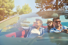 Leisure, road trip, travel and people concept - happy friends driving in cabriolet car along country road Royalty Free Stock Images