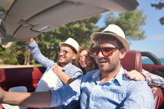 Leisure, road trip, travel and people concept - happy friends driving in cabriolet car along country road Stock Image
