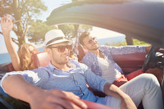 Leisure, road trip, travel and people concept - happy friends driving in cabriolet car along country road Royalty Free Stock Image