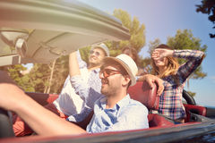 Leisure, road trip, travel and people concept - happy friends driving in cabriolet car along country road Stock Photos