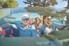 Leisure, road trip, travel and people concept - happy friends driving in cabriolet car along country road Stock Images