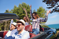 Leisure, road trip, travel and people concept - happy friends driving in cabriolet car along country road Royalty Free Stock Photography