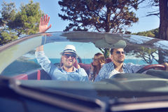 Leisure, road trip, travel and people concept - happy friends driving in cabriolet car along country road Stock Photography