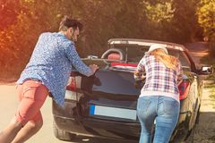 Leisure, road trip, travel and people concept - happy friends pushing broken cabriolet car along country road Royalty Free Stock Photos