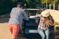 Leisure, road trip, travel and people concept - happy friends pushing broken cabriolet car along country road Royalty Free Stock Image
