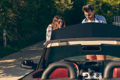 Leisure, road trip, travel and people concept - happy friends pushing broken cabriolet car along country road Stock Image