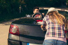 Leisure, road trip, travel and people concept - happy friends pushing broken cabriolet car along country road Royalty Free Stock Photography