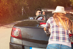 Leisure, road trip, travel and people concept - happy friends pushing broken cabriolet car along country road Stock Images