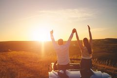 Leisure road trip travel. And people concept happy men couple driving in cabriolet car at country enjoying sunset holding hands up stock photo