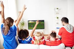 Friends or soccer fans watching game on tv at home. Leisure, sport and entertainment concept - happy friends or football fans watching soccer game on tv and Royalty Free Stock Photos