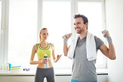 Leisure in sports club. Happy guy exercising with dumbbells with his girlfriend on background Stock Photography