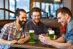 Friends with smartphone drinking green beer at pub Stock Photo
