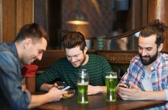 Friends with smartphones and green beer at pub Stock Photo