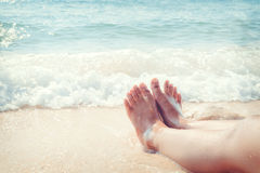 Leisure in summer - Beautiful leg of sexy women tan. Relax on sandy tropical beach. vintage color styles Royalty Free Stock Image