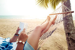 Leisure in summer - Beautiful Tanned of sexy women. Relax and reading on hammock at sandy tropical beach. vintage color styles Royalty Free Stock Photos