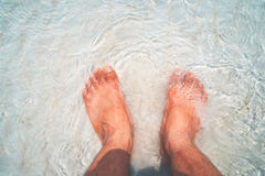 Leisure in summer relax on beach. Above of man`s foot. vintage and retro filter effect royalty free stock image