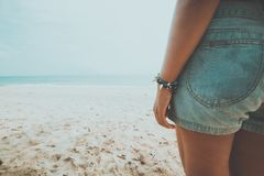Young tanned woman standing relax on a tropical beach. Blue sea in the background. Stock Photography