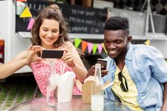 Mixed race couple photographing wok at food truck Royalty Free Stock Images