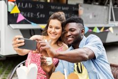 Mixed race couple taking selfie at food truck Royalty Free Stock Photography