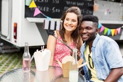 Mixed race couple taking selfie at food truck Royalty Free Stock Images