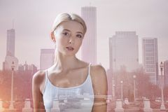 Young model expressing calmness in her eyes. Leisure time. Charming model standing against urban background while expressing calmness her eyes Stock Image
