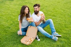 Leisure time. fast food. bearded man hipster and adorable girl eat pizza. summer picnic on green grass. Diet. couple in. Leisure time. fast food. bearded men royalty free stock photography