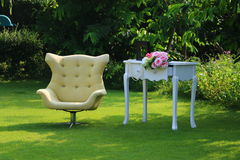 Leisure Time In the Garden. Yellow chair and White Table with bouquet of flowers on the green grass Royalty Free Stock Photo