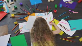 Leisure time of little blond girl drawing with colorful pencils, childhood. Stock footage stock video footage