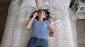 Leisure time, merry woman into headset falls on bed and listens to songs from mobile phone and take pleasure music while. Relaxing at home on weekends stock video