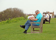 Leisure time on the park benches. Photo of people relaxing and reading newspapers on benches at tankerton slopes in whitstable kent on 3rd april 2014 Stock Photo