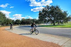 Leisure time. Two man riding the bike with helmets through the park landscape on a sunny day, to spend their leisure time outside in nature and doing sports stock photo