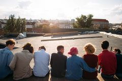 Leisure travel diverse people teenage lifestyle. Leisure holidays travel trip. Back view of diverse group of people sitting on a rooftop. Teenage carefree stock photo