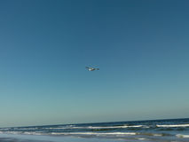 Leisure white plane flying over sea shore Stock Photos
