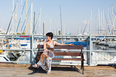 Leisure woman on holiday near yacht and sailboats marina resort town. Luxury lifestyle. Royalty Free Stock Photos