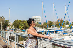 Leisure woman on holiday near yacht and sailboats marina resort town. Luxury lifestyle. Stock Photo