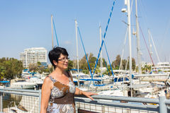 Leisure woman on holiday near yacht and sailboats marina resort town. Luxury lifestyle. Royalty Free Stock Image