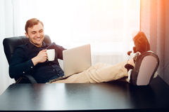 Leisure work at home with laptop on knees Royalty Free Stock Images