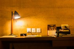 Leisure working desk under a glowing lamp.  Stock Photos