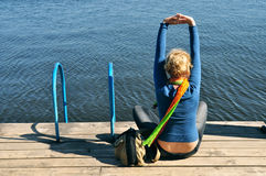 Leisure, yoga, relax. Fitness health, in coast, the girl spends his free time, she sits on the pier overlooking the water and city in the distance stock photo