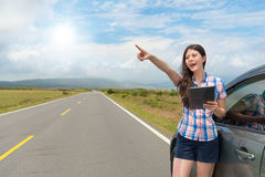 Attractive woman stopping car on roadside. Leisurely attractive woman stopping car on roadside standing at asphalt road using digital tablet computer and making Royalty Free Stock Photography