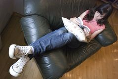 Leisurely reading at home. A young woman at home leisurely reading a book in a leather chair Stock Images