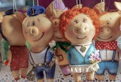 Leitão macios dos brinquedos na roupa diferente no contador de uma loja das crianças imagem de stock royalty free