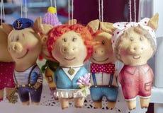 Leitão macios dos brinquedos na roupa diferente no contador de uma loja das crianças fotografia de stock royalty free