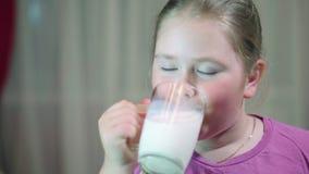 Leite bebendo da criança do vidro Menina com cabelo louro bonito Uma criança 8 anos velha vídeos de arquivo