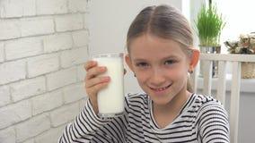 Leite bebendo da criança no café da manhã na cozinha, menina que prova produtos láteos fotografia de stock