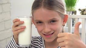 Leite bebendo da crian?a no caf? da manh? na cozinha, menina que prova produtos l?teos