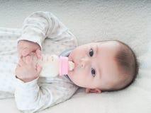 Leite bebendo do bebê da garrafa isolada Foto de Stock