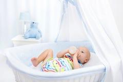 Leite bebendo do bebê Menino com a garrafa da fórmula na cama imagens de stock