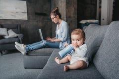 Leite bebendo do rapaz pequeno adorável da garrafa de bebê no sofá quando sua mãe que trabalha no portátil em casa fotos de stock royalty free